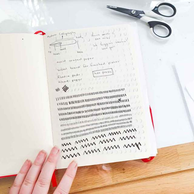 Image shows a notebook page with some marks made using a pointed pen.