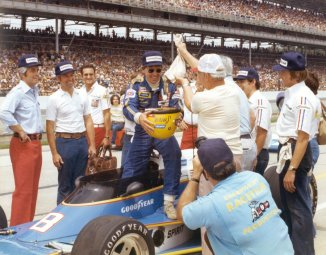 Tom Sneva using his helmet to hold the 200 silver dollars that was his reward for breaking the 200 mph barrier during qualifications for the 1997 Indianapolis 500 Mile Race. -- Photo courtesy of IMS Photo.