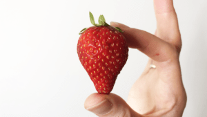 A hand holding a strawberry