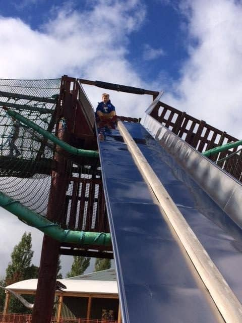 Little boy at the top of a giant metal slide