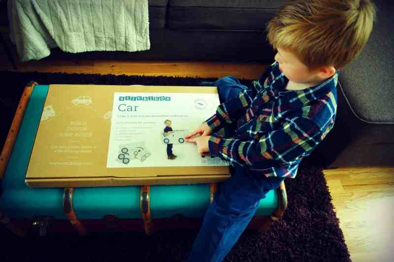 Four year old boy pointing at a cardboard package with Stickibox car written on it
