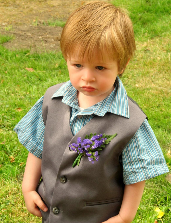 Little boy in an oversized grey suit pulling a grumpy face
