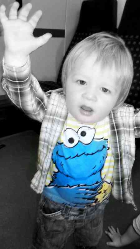 A little boy wearing a cookie monster top and shouting