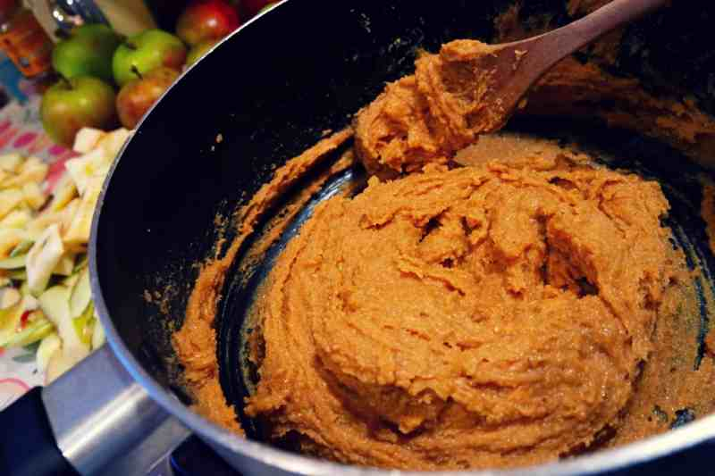 a mixing bowl flle with dark brown cake mix and spoon
