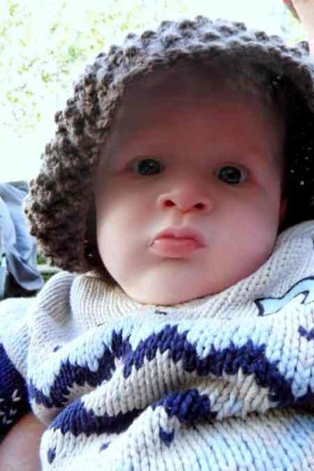 Baby pulling a grumpy face wearing a brown knitted hat
