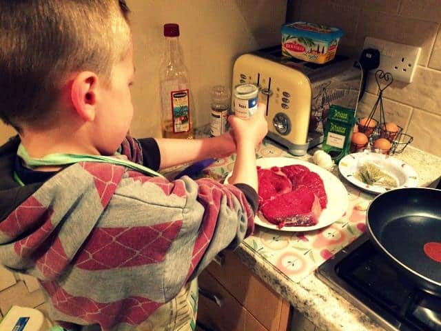 Little boy in an apron cooking