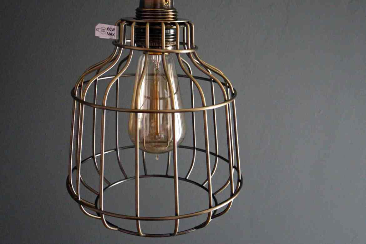 First lighting brass caged lampshade against a grey wall.