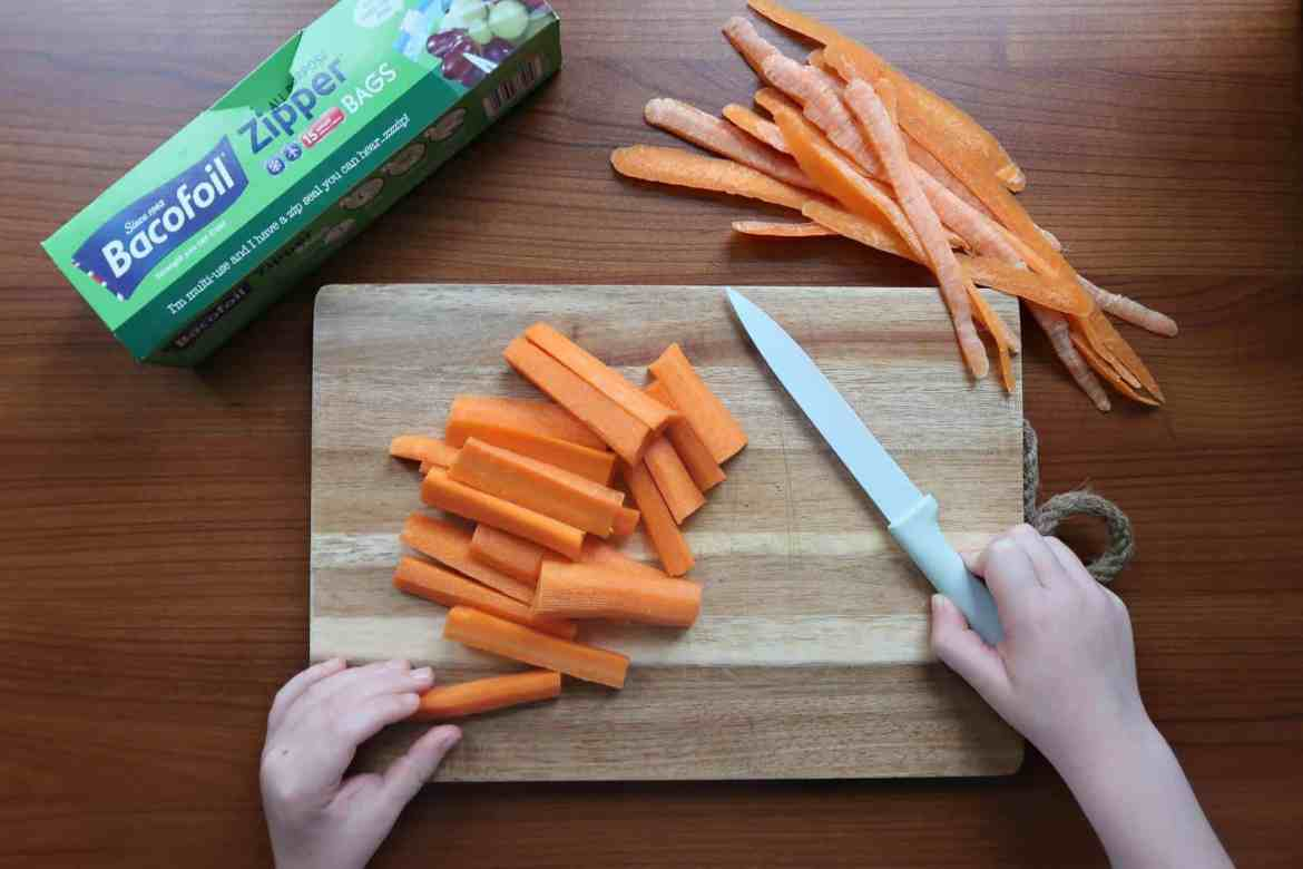 Little boy helping to chop carrot batons for his lunchbox