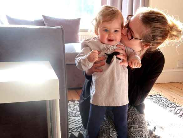 one year old baby girl standing up being kissed by mum