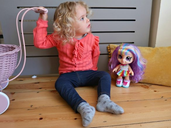 Kindi Kids Rainbow Kate doll with her hair down standing next to a girl in a pink cardigan