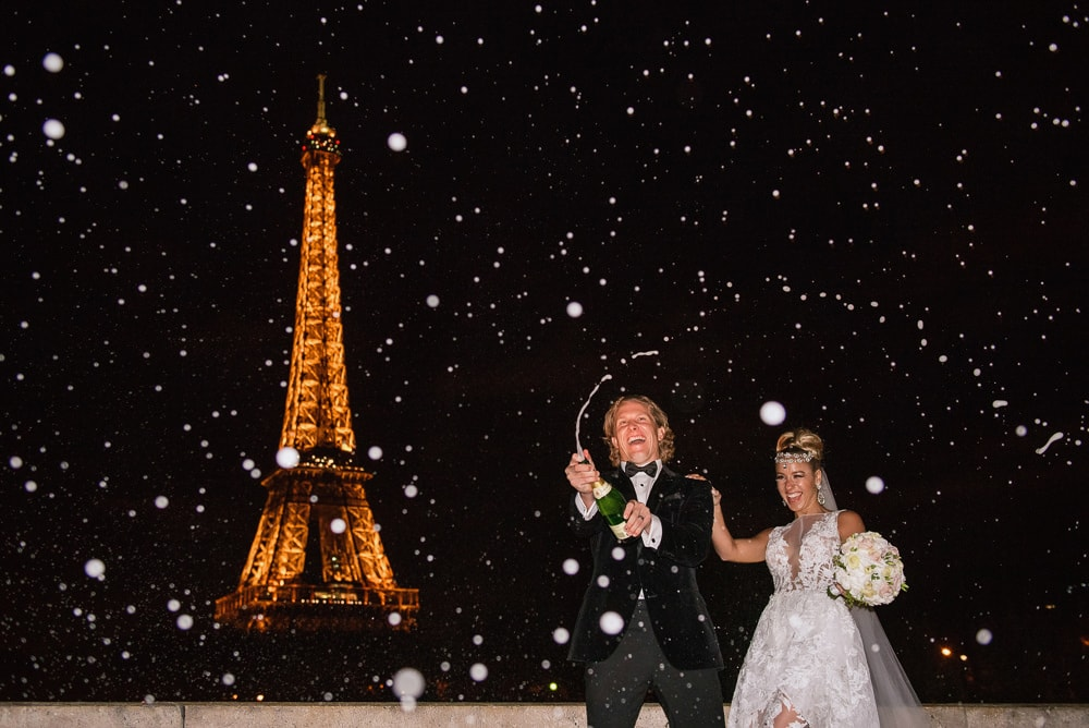 Paris elopement photographer - Bride and groom celebrate with champagne pop in front of the Eiffel Tower by night