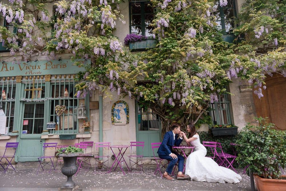 Paris photographer knows hiddel places in the city. Asian groom kissing bride's hand at Au Vieux Paris