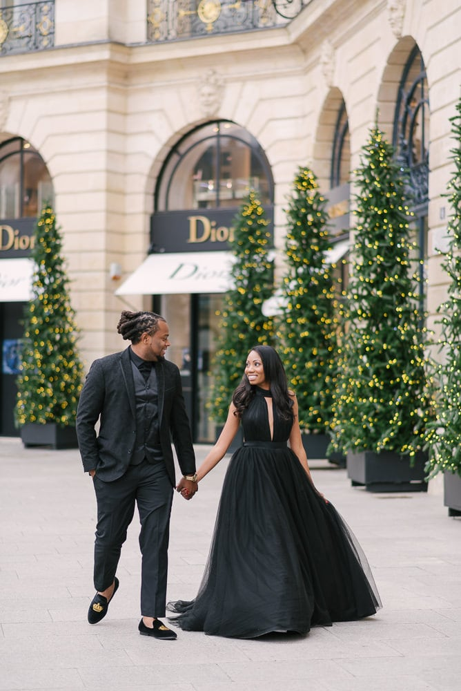 Winter engagement photos - Cute american couple walking in Place Vendome surrounded by Christmas lights