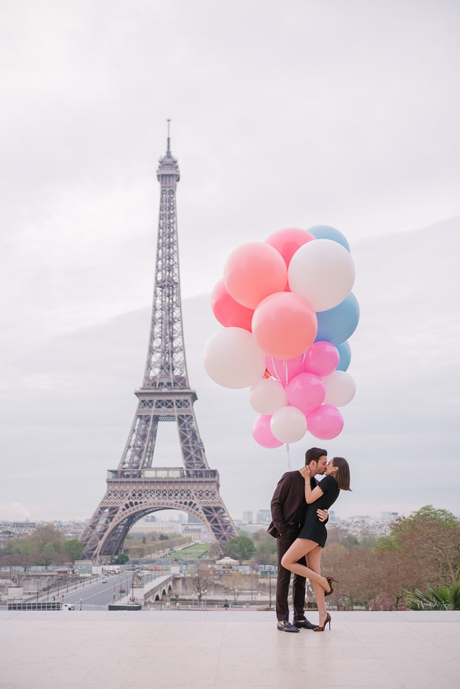 Crazy couples pictures - Young couple kissing underneath huge and colorful balloons in Paris