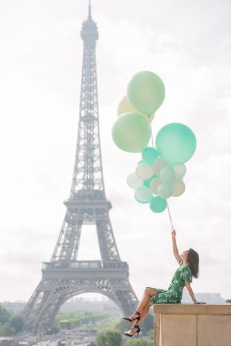 Indonesian girl holding green balloons is posing in front of the Eiffel Tower during a mid day photo shoot with The Paris Photographer