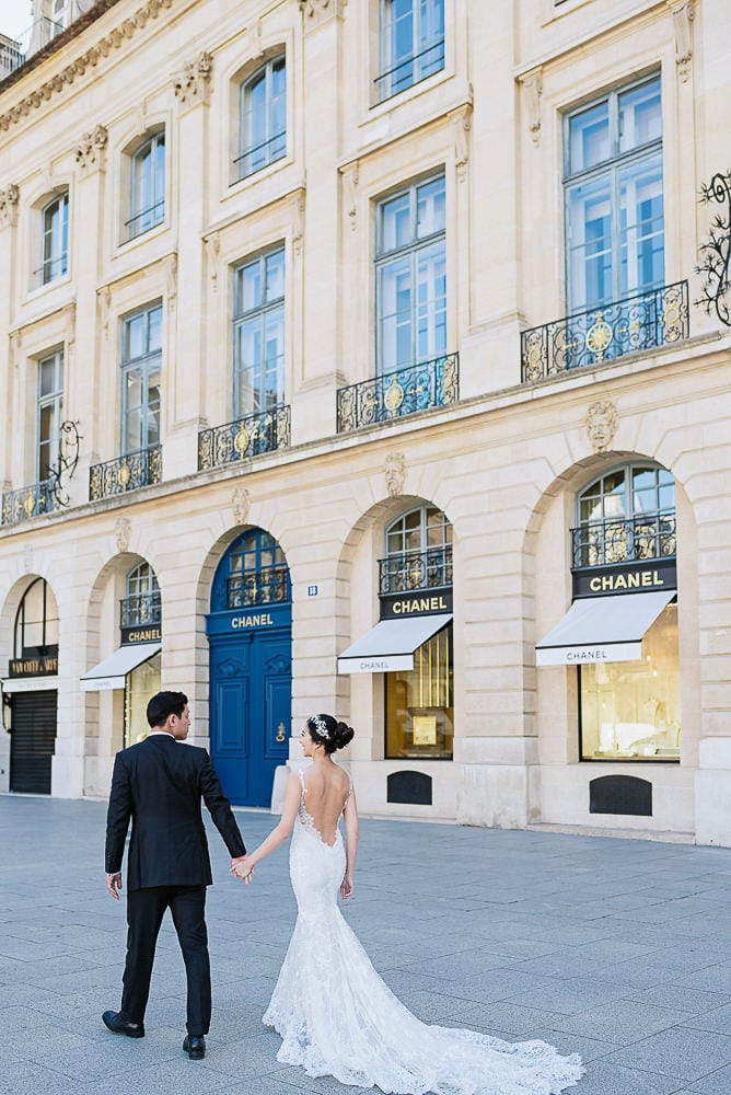 pre wedding pictures poses - bride and groom walking hand in hand in place vendome