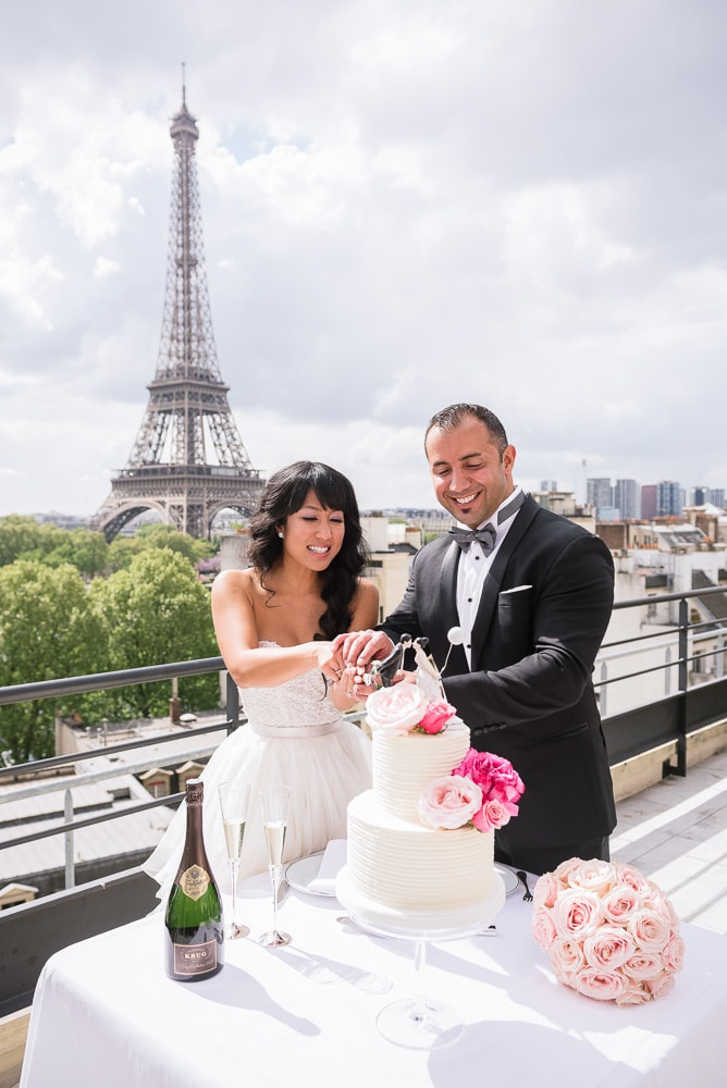 wedding photography paris - bride and groom cutting cake on the terrace of shangri la hotel having the eiffel tower behind them