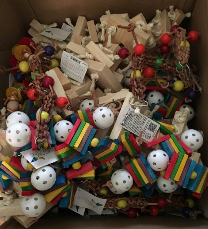 A box of colorful parrot toys