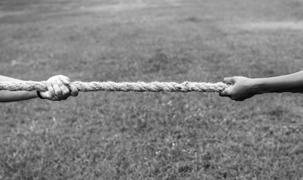 Tug of war, two arms pulling a rope