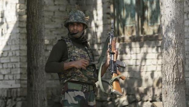 An Indian Army soldier patrols at Nowgam sector, near the de facto border. (AP Photo)