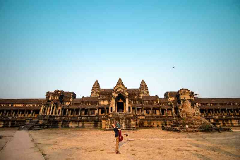 Couple standing behind Angkor Wat temple with no people