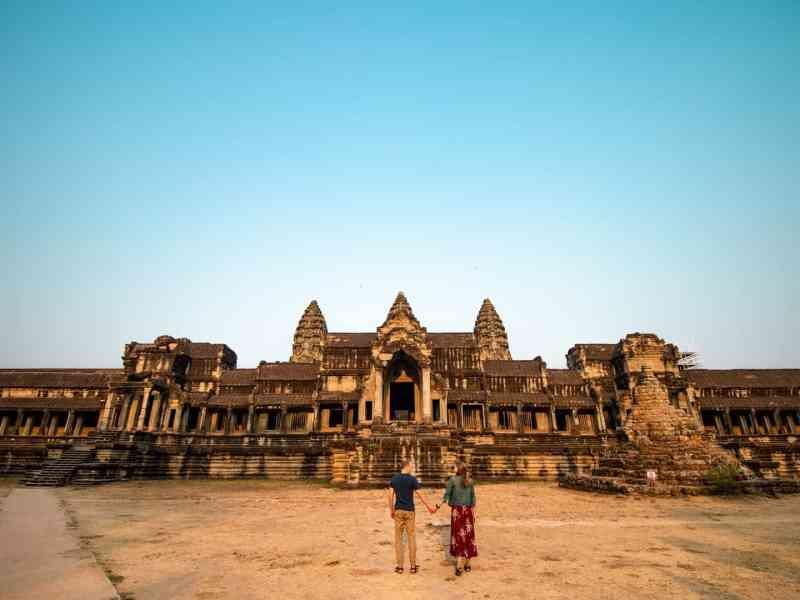 Couple looking up at Angkor Wat temple