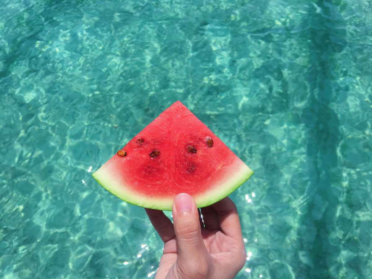 hand holding a slice of watermelon with blue swimming pool water during the heatwave