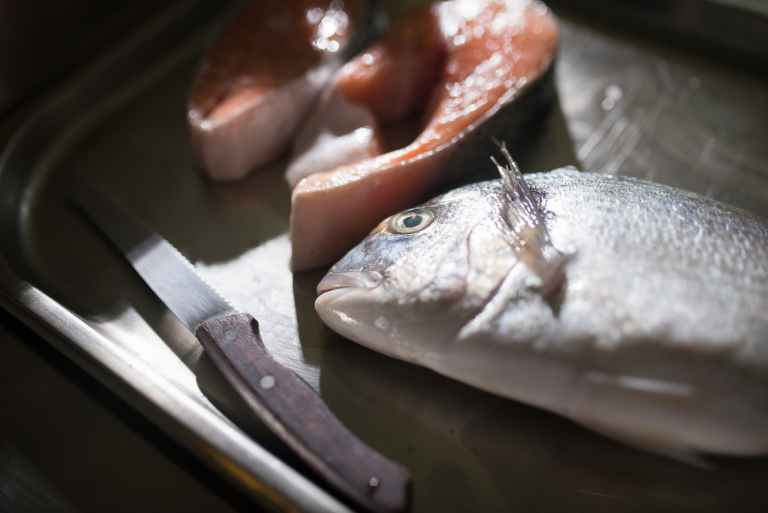 silver fish on brown chopping board