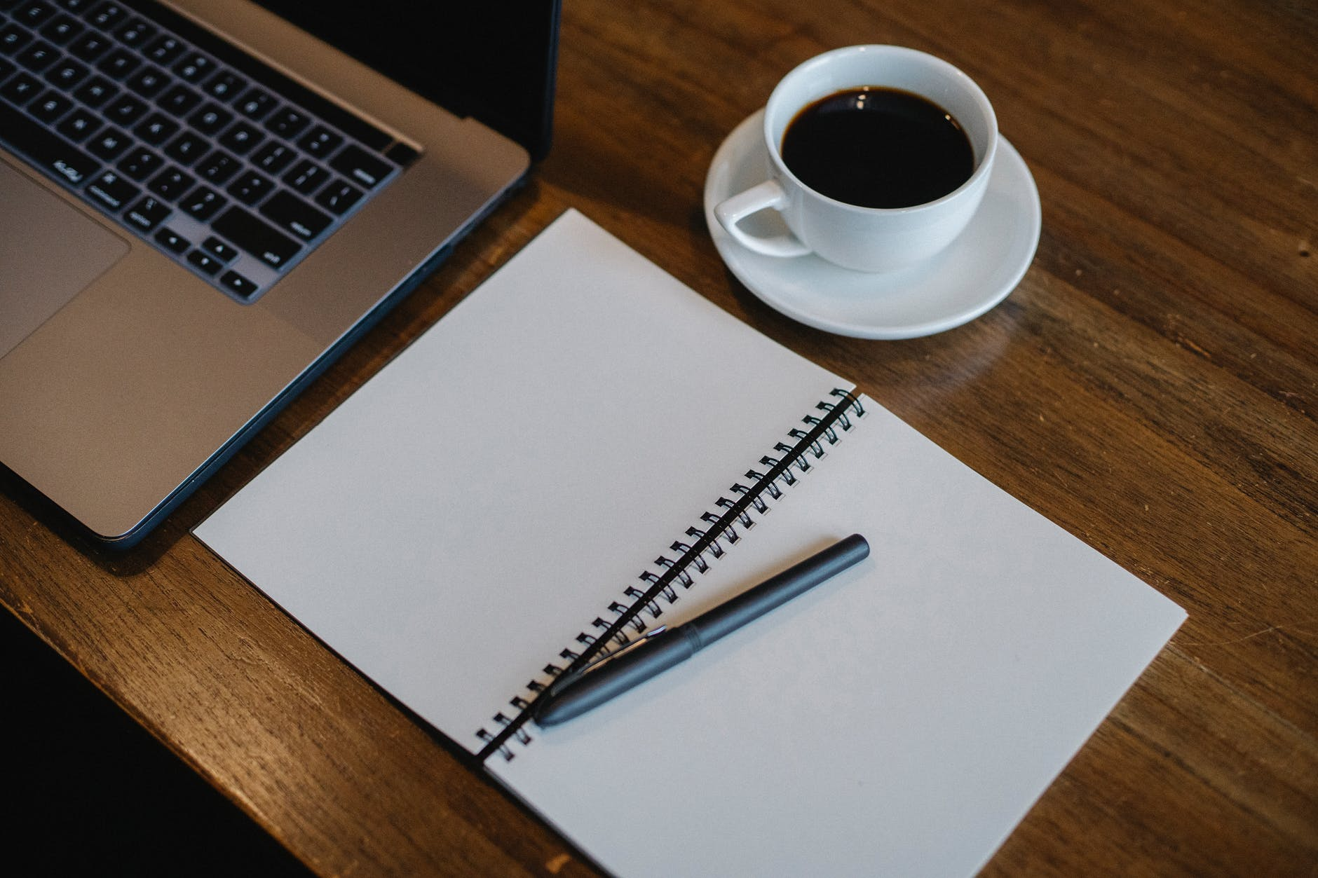 laptop and notepad near cup of coffee