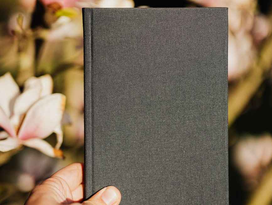 closed notebook in hand of unrecognizable person against floral background