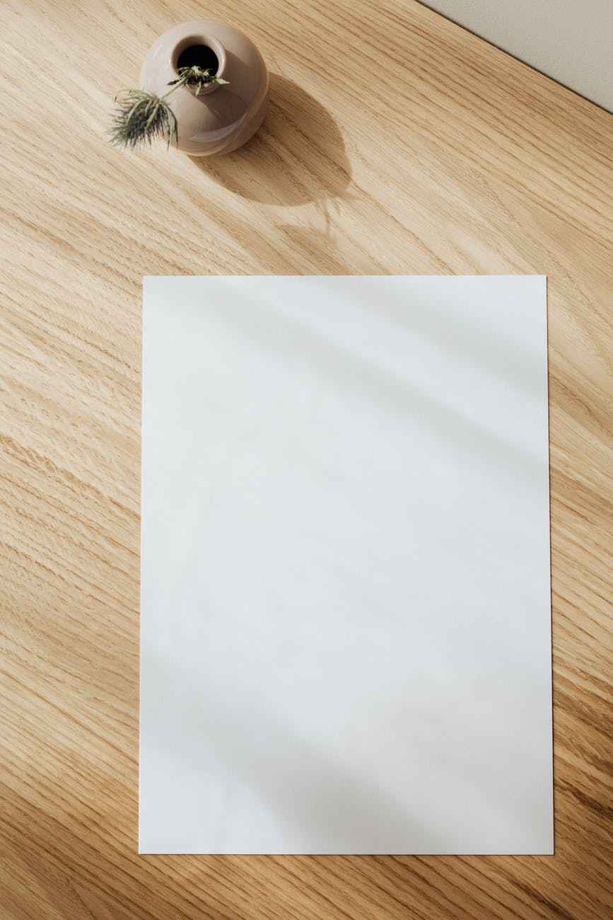 blank white paper sheet on wooden table
