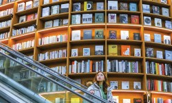 woman on elevator mountain of books