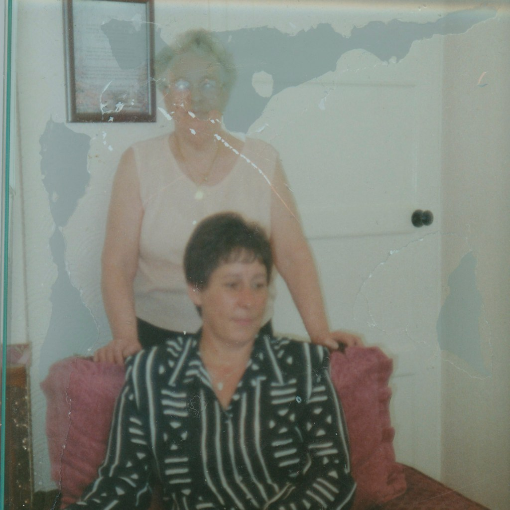 Photo of 2 ladies which has suffered from moisture damage making one of the ladies faces unrecognisable.