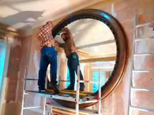Matt using the scaffold tower to install this gigantic mirror for the bar area of a hotel in Bath.