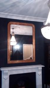 Ornate gold gilt rectangular pane mirror hung in a living room above a fireplace in Haywards Heath.