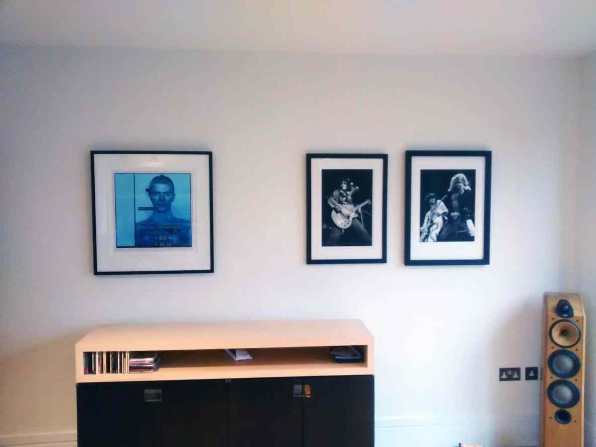 Three pictures of musicians hung above a sound system in a home in Horsham