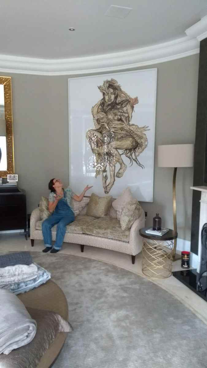 Large picture hung on a curved wall above a sofa in a living room in Virginia Water, Windsor.