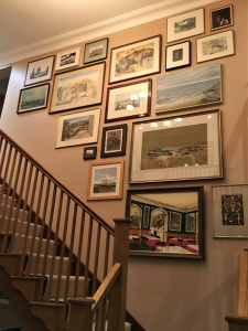 A collage of frames arranged and hung above stairs in Oxfordshire.