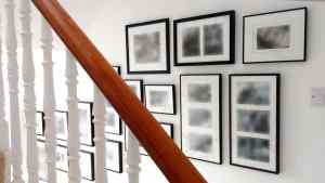 A collage wall of black and white photographs running above a staircase in a London home.