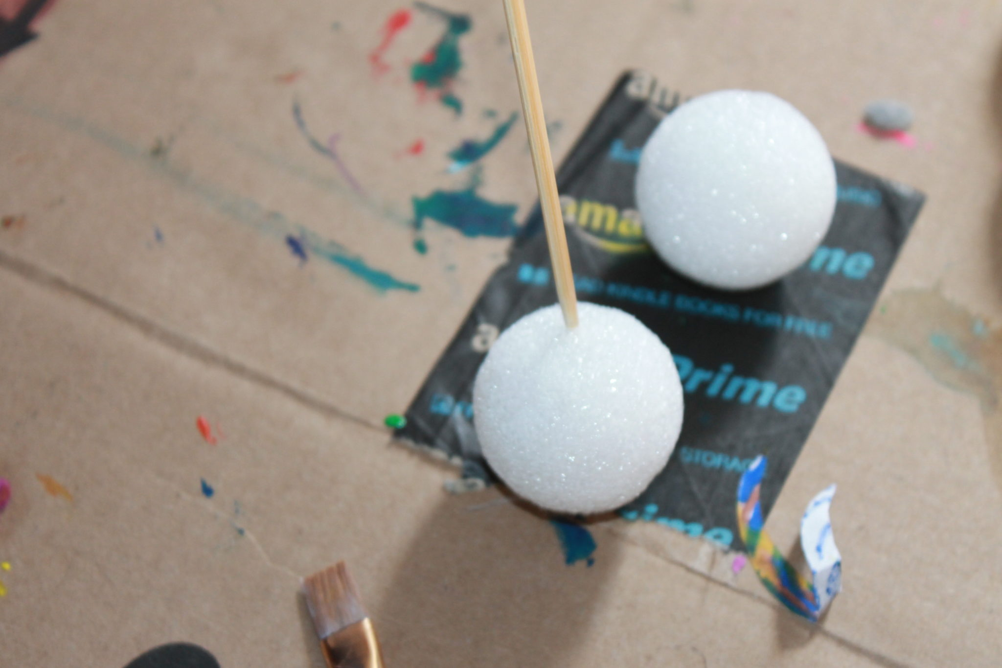 Hold on to the skewer & use acrylic paints to paint around each ball.