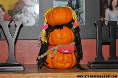 I hot glued all 3 pumkins together, putting the daddy on the bottom, mommy in the middle & baby on top. I used a pipe cleaner as a scarf for the mama.