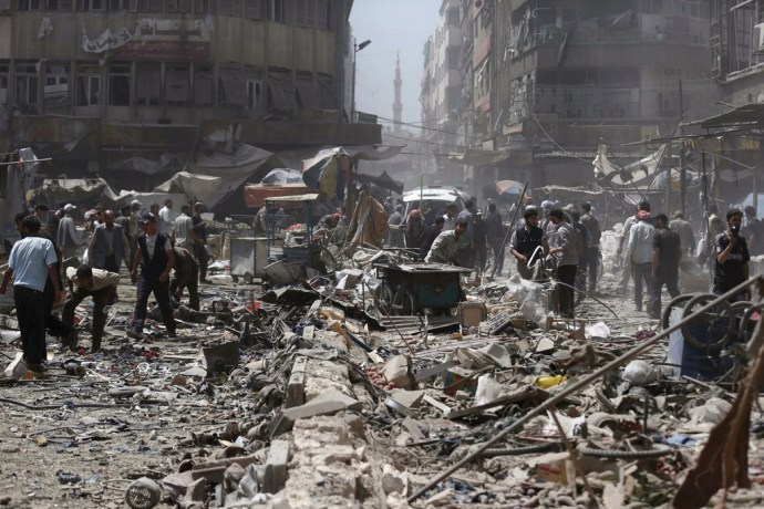 People inspect a site hit by what activists said were air strikes by forces loyal to Syria's President Bashar al-Assad on a marketplace in the Douma neighborhood of Damascus, Syria August 16, 2015. A Syrian government air strike northeast of Damascus killed about 80 people on Saturday, rescue workers and the Syrian Observatory for Human Rights said. REUTERS/Bassam Khabieh   NO ARCHIVES