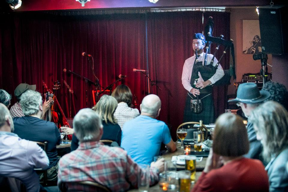 Image of Matthew McRae bagpiping in Camden (London) as part of an album launch