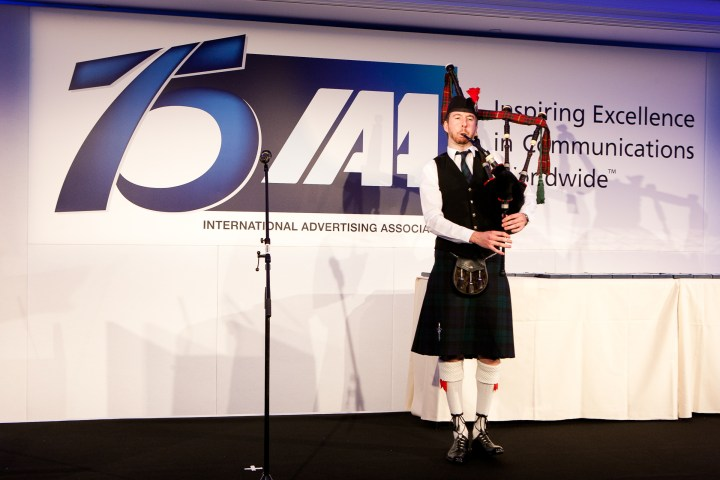 Image of Matthew McRae bagpiping at the 75th International Advertising Association anniversary dinner in London