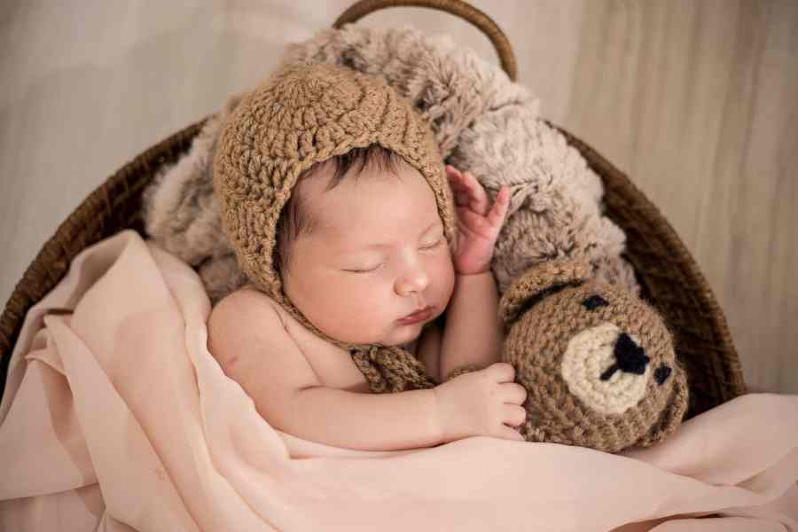 baby wearing brown knit cap while sleeping newborn baby portraits ideas
