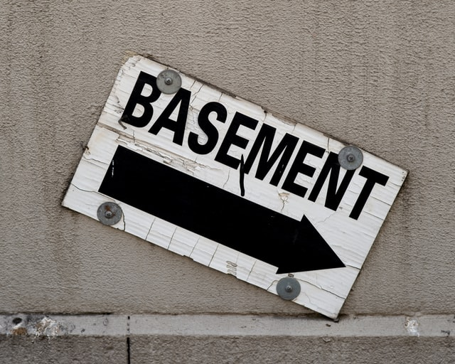 A white wooden sign with basement written on it