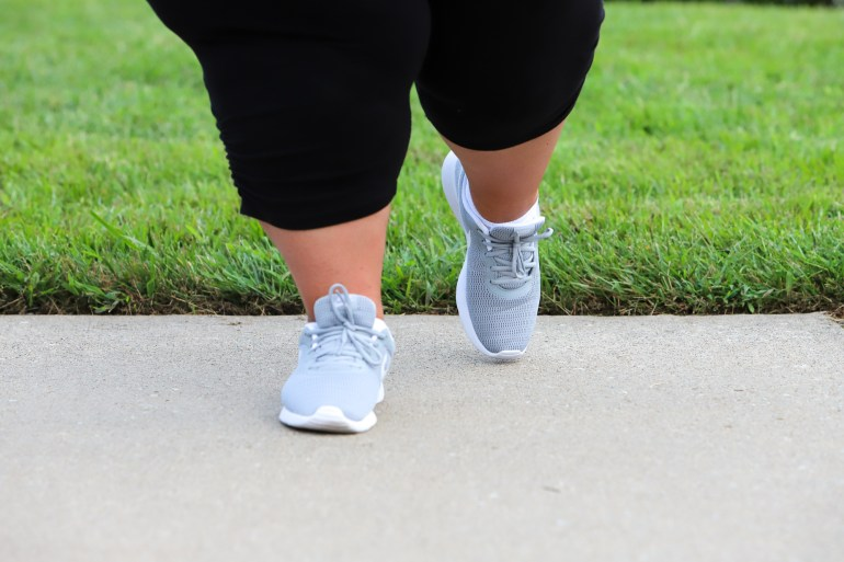Plus size woman's lower legs walking while wearing grey and white sneakers and black capri leggings.