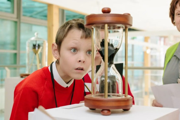 A boy staring at an hourglass.