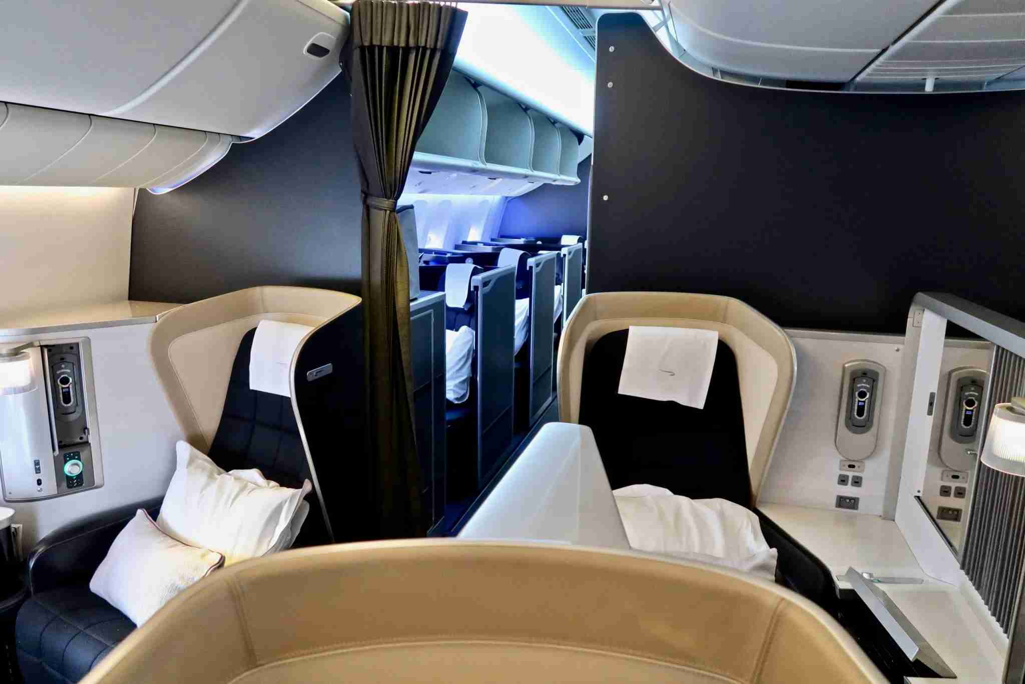 Row 2 of the BA refurbished B777-200 with Club World Suites behind the dividing wall and curtain. Image by Christian Kramer / The Points Guy