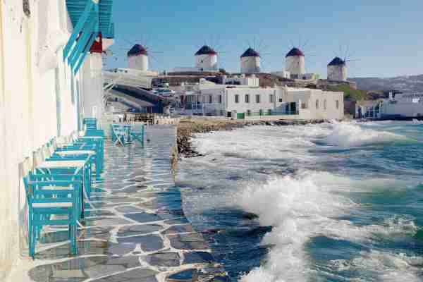 Cafe tables and chairs right near the sea with waves overlooking famous Mykonos windmills.